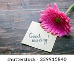 "Small photo of Gerbera flower and piece of paper with text ""good morning"" on the wooden table close-up"