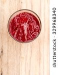 Small photo of Glass of Roselle juice with ice. Traditional beverage. Herbal drink. Top view on wooden table.
