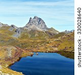 Small photo of Pic du Midi d Ossau is in center, the sky reflecting in water mirror of the small lake in Anayet plateau in Spanish Pyrenees, Aragon