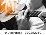 Small photo of attractive musician playing classical / acoustic guitar & amber light