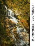 Small photo of Full view of Cloudland Falls on Dry Brook, with autumn foliage in front, as a shroud or scrim, in Franconia Notch of the White Mountains National Forest in northern New Hampshire.