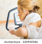 Beautiful woman doing her daily fitness excercises on stationary bycicle at the gym. - stock photo