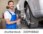 Small photo of smiling serviceman checking wheel alignment in a car workshop