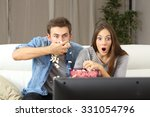 amazed couple watching tv... | Shutterstock . vector #331054796