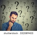 Stock photo worried sad man has many questions looking down isolated on gray wall background human face 332089403