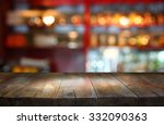 Stock photo image of wooden table in front of abstract blurred background of restaurant lights 332090363