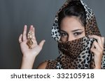 Small photo of Indian girl face covered leopard spotted veil holding kajal pot