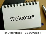 Welcome memo written on a notebook with pen - stock photo