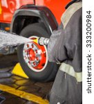 Small photo of Midsection of firewoman spraying water while practicing at fire station