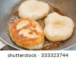 cooking bhaturas in frying pan | Shutterstock . vector #333323744