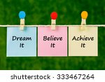 Small photo of Word quotes of Dream It, Believe It, Achieve It on sticky color papers hanging on rope against blurred green background.
