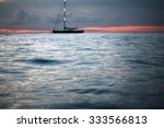 Small photo of Beautiful calm evening seascape with silhouette of yacht under bare poles floating in blue sea waves after red sunset in background on the horizon distant view, horizontal picture
