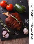 Small photo of Baked pork shank and fresh vegetables close up on a slate board on the table. vertical top view