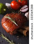 Small photo of Baked pork shank and ingredients close-up on a slate board. vertical