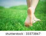 Woman legs walking on green grass - stock photo