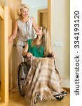 Small photo of Smiling young girl in wheelchair with assistant at threshold