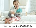 Stock photo portrait of happy little girl at home with labrador puppy 334201394