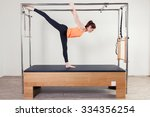 Small photo of Pilates aerobic instructor woman in cadillac fitness exercise.