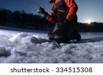 man ice fishing on a lake in... | Shutterstock . vector #334515308