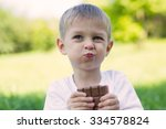 boy eating chocolate outdoors... | Shutterstock . vector #334578824