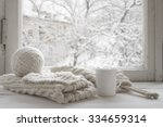 Small photo of Cozy winter still life: mug of hot tea and warm woolen knitting on vintage windowsill against snow landscape from outside.