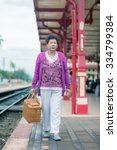 Small photo of Mature vital elderly woman at the train station. travel on holiday in vintage tone.