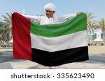 arabian boy holding uae flag... | Shutterstock . vector #335623490