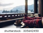 Small photo of Feet in woollen socks by the Alps mountains view. Woman relaxes by mountain view with a cup of hot drink. Close up on feet. Winter and Christmas holidays concept.