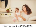 mom and little girl sitting in... | Shutterstock . vector #335669276