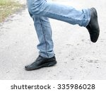 Man's Feet In Blue Jeans In...
