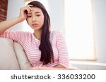 upset asian woman on couch at... | Shutterstock . vector #336033200