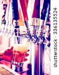 bartender pouring draft beer in ... | Shutterstock . vector #336135524