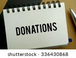 Donations memo written on a notebook with pen - stock photo