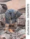 Small photo of Tyumen, Russia - February 16, 2008: Demolition of machine-tool factory. Worker cutting metal with with acetylene torch