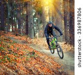 mountain biker riding in autumn forest - stock photo