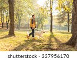 Stock photo profile shot of a cheerful young man walking his dog in a park on a sunny autumn day 337956170