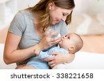 cute mother feeding her... | Shutterstock . vector #338221658
