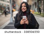 indian woman in city texting... | Shutterstock . vector #338506550