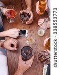 Stock photo view on friends having alcoholic drinks in the bar close up 338553773