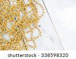 golden beads on rustic white... | Shutterstock . vector #338598320