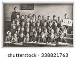 Group of children and teacher in the classroom. Retro picture of classmates in the school. Vintage photo with original film grain, blur and scratches from ca 1948 - stock photo