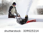 a man works snow blowing machine | Shutterstock . vector #339025214