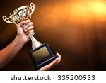 hand holding up a gold trophy... | Shutterstock . vector #339200933