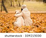 Stock photo portrait of a beautiful young woman with her dog while walking in the autumn park 339215030
