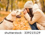 Stock photo portrait of a beautiful young woman with her dog while walking in the autumn park 339215129