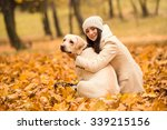 Stock photo portrait of a beautiful young woman with her dog while walking in the autumn park 339215156