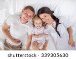 happy family lying on a bed... | Shutterstock . vector #339305630