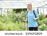 Young Woman Spraying Plants In...
