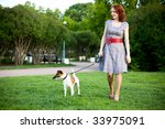 Stock photo young woman walking with her dog in a park 33975091