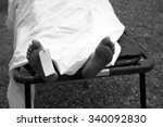 Small photo of Gruesome image of a dead persons feet with a toe tag to identify the person and cause of death, next of kin and any other important information.